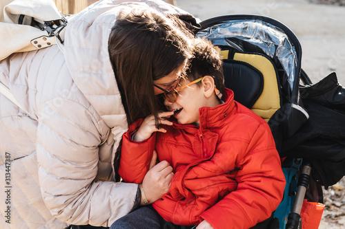 una madre juega con su hijo con pluridiscapacidad en un parque, el niño va con silla de ruedas, es el invierno y van con ropa de abrigo Canvas Print