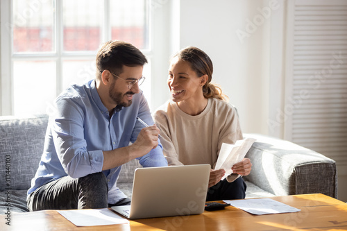 Fotografia Happy young couple pay bills using online banking