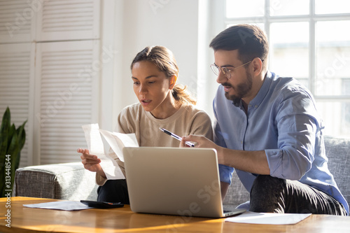 Focused young couple manage finances paying bills online Canvas Print