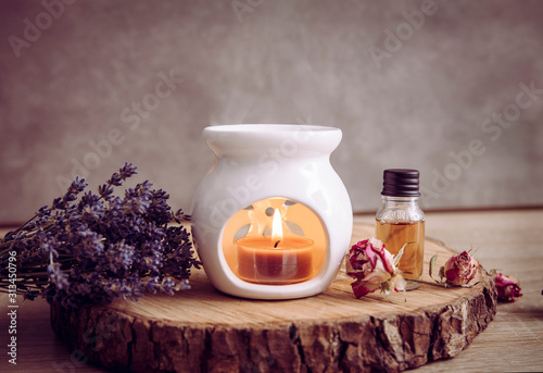 Photo Vintage style picture of white ceramic candle aroma oil lamp with essential oil bottle and dry flower petals on natural pine wood disc, dry background with copy space