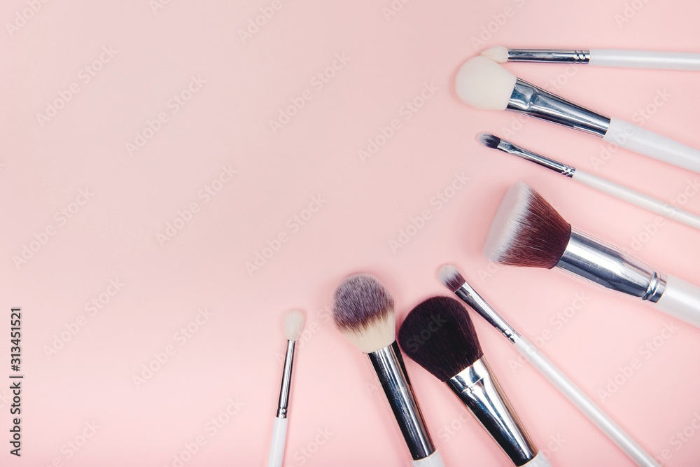Fototapeta Set makeup brushes on pink color background. Top view point, flat lay
