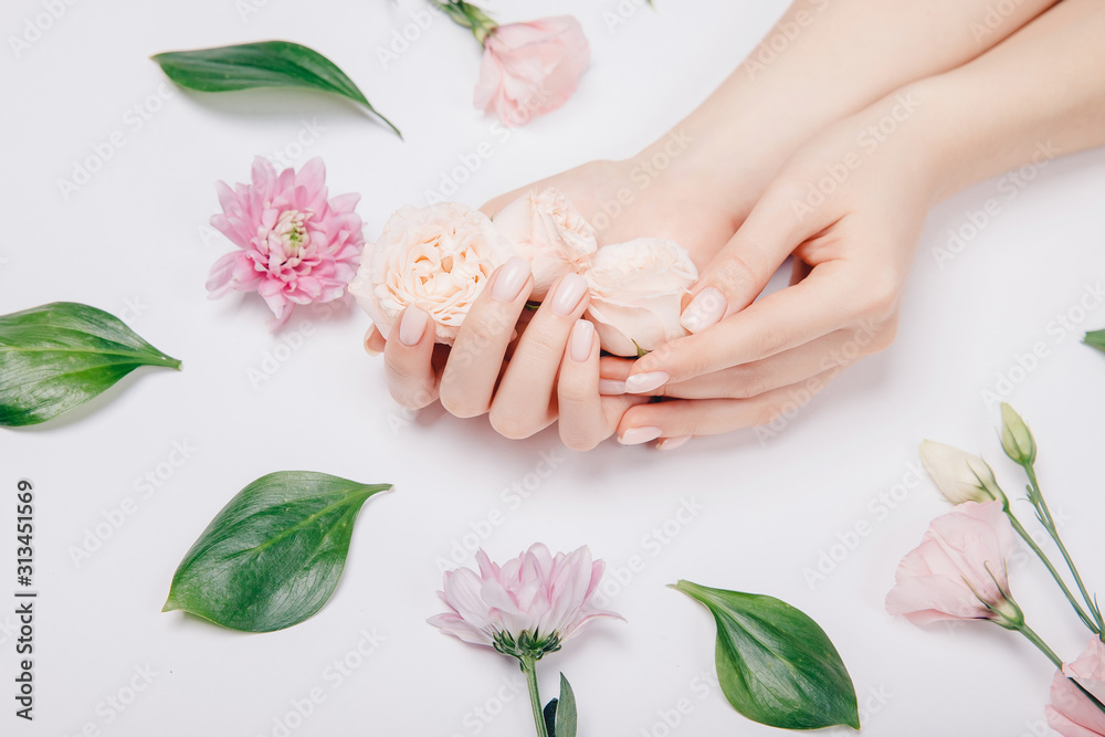 Fototapeta Concept beauty skin care. Beautiful stylish trendy female pink manicure with flower on background, top view