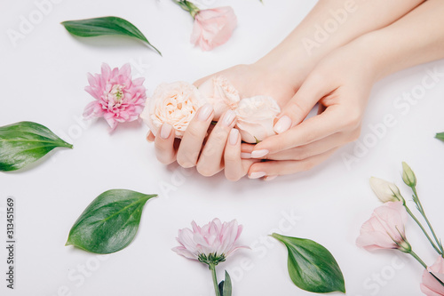 Obraz Concept beauty skin care. Beautiful stylish trendy female pink manicure with flower on background, top view - fototapety do salonu