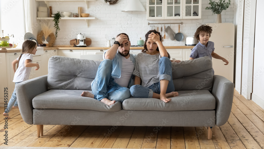 Fototapeta Parents tired of noisy children who are running and shouting