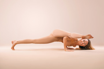 Indoor Yoga Classes. Sports recreation. Beautiful young woman in asana pose. Individual sports. Nude sportswear.