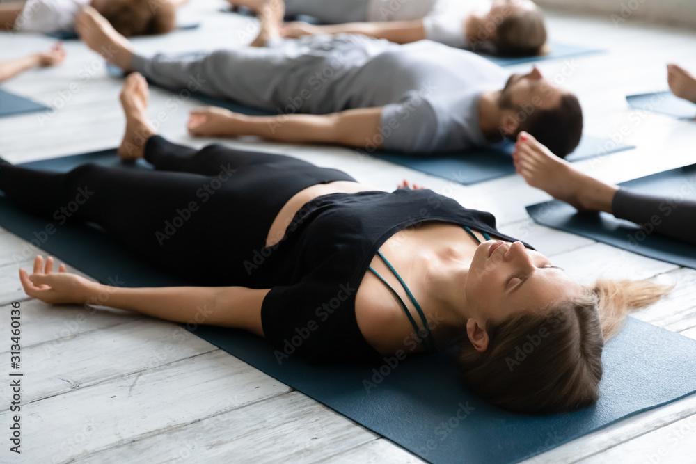 Fototapeta Beautiful woman meditating in Savasana pose close up, practicing yoga