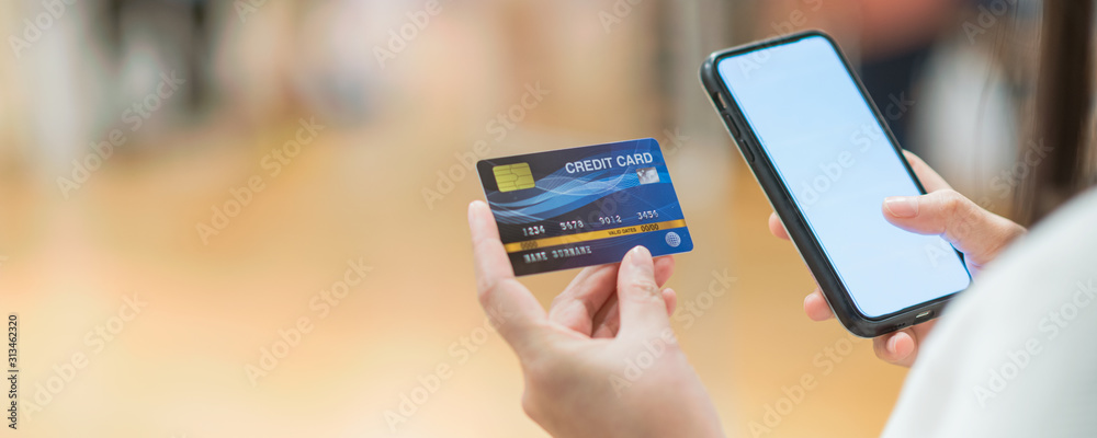 Fototapeta Banner of Closeup Asian women using mobile phone application for online shopping in department store , Online payment concept, credit card mockup