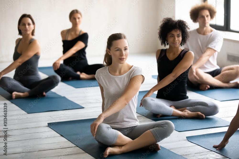 Fototapeta Diverse young people practicing yoga, doing Parivritta Sukhasana exercise