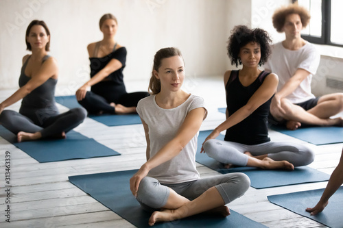Fototapeta Diverse young people practicing yoga, doing Parivritta Sukhasana exercise obraz