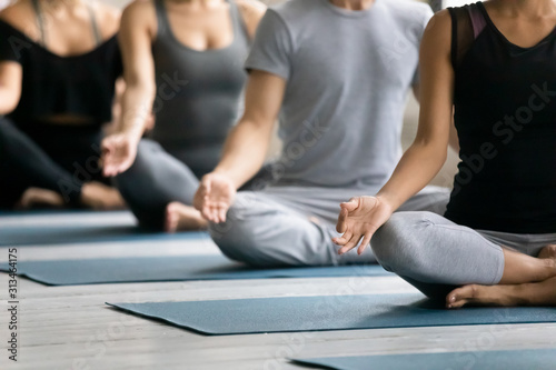 Obraz Diverse people meditating at group lesson, practicing yoga, Lotus pose - fototapety do salonu