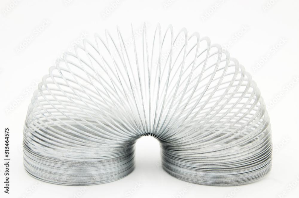 Fototapeta shiny metal slinky isolated on a white background