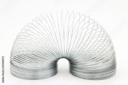 shiny metal slinky isolated on a white background Wallpaper Mural