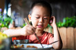 Asian boy having lunch at the restaurant