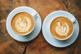 Two cups of aromatic coffee cappuccino or latte on a wooden table. Concept of meeting or relaxing. Tasty morning drinks.