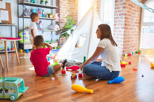 Obraz Young beautiful teacher and toddlers playing around lots of toys at kindergarten - fototapety do salonu