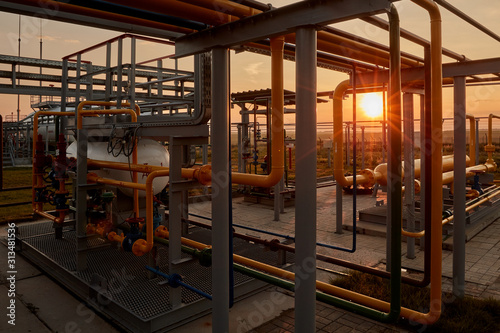 Fototapeta Gas industry. Pipeline system at gas processing plant illuminated by the rays of the rising sun obraz