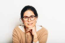 Studio Portrait Of Beautiful Brunette Woman, Wearing Glasses, Leaning On A Hand, Posing On White Background
