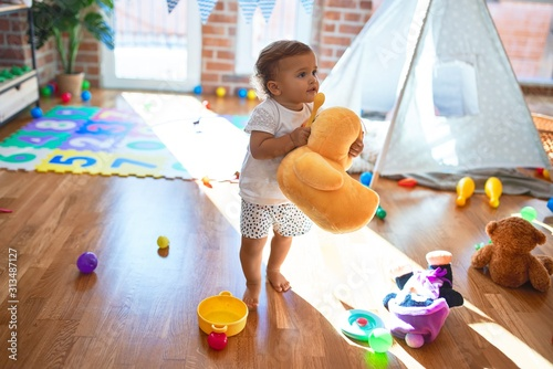 Obraz Adorable toddler holding duck doll standing around lots of toys at kindergarten - fototapety do salonu