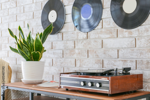 Record player with vinyl disc on table in room Wallpaper Mural