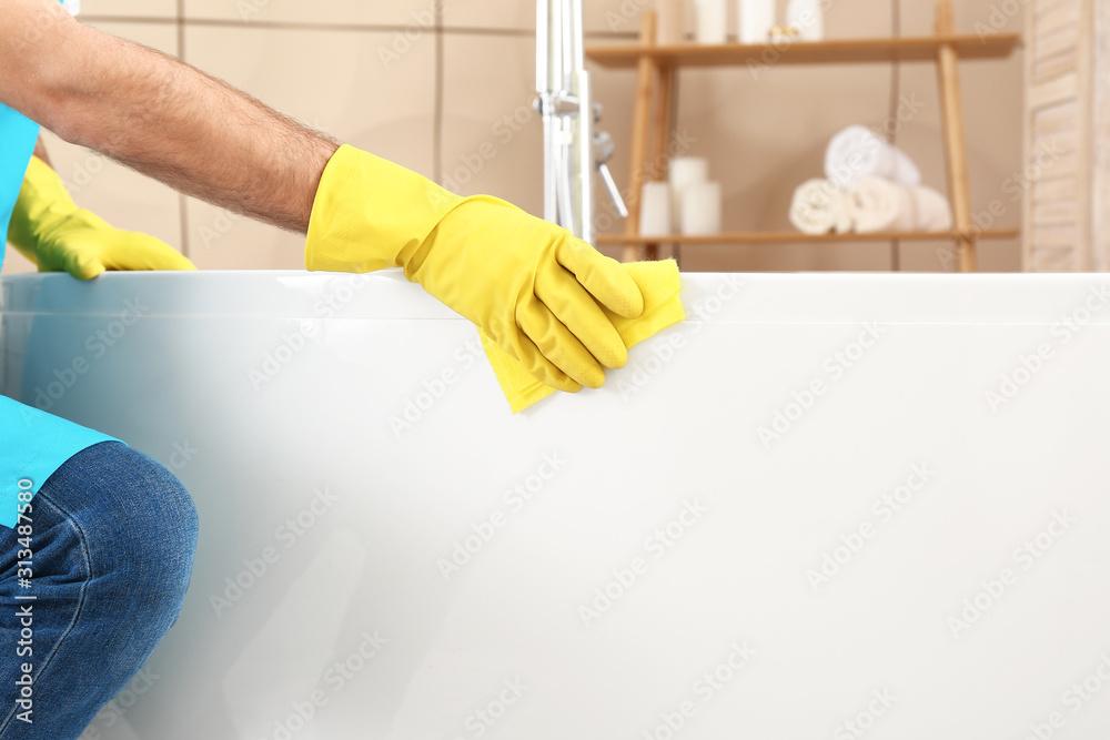 Fototapeta Male janitor doing cleanup in bathroom