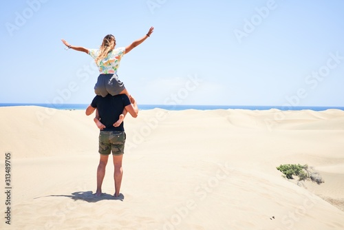 Fototapety, obrazy: Young beautiful couple smiling happy and confident. Woman sitting on man shoulders with smile on face at the beach