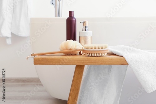 Photo Body care cosmetics with accessories on bench in bathroom