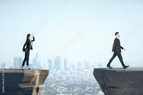 Obraz Businesswoman looking on businessman standing on mountain. - fototapety do salonu