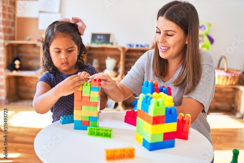 Obraz Beautiful teacher and toddler girl playing with construction blocks bulding tower at kindergarten - fototapety do salonu