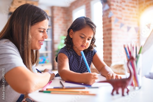 Canvastavla Beautiful teacher and toddler girl drawing draw using colored pencils at kinderg