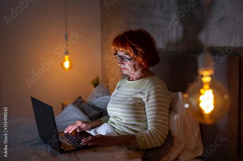 Senior novelist writing new book using laptop computer Fototapet
