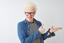 Young Albino Blond Man Wearing Denim Shirt And Glasses Over Isolated White Background Showing Palm Hand And Doing Ok Gesture With Thumbs Up, Smiling Happy And Cheerful
