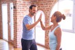 canvas print picture - Middle age beautiful sporty couple smiling happy. Standing with smile on face highing five at gym