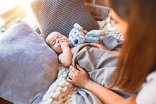 Young Beautifull Woman And Her Baby On The Floor Over Blanket At Home. Newborn And Mother Relaxing And Resting Comfortable With Doll