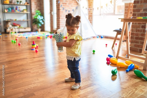Obraz Beautiful toddler holding glass of striped straws standing at kindergarten - fototapety do salonu