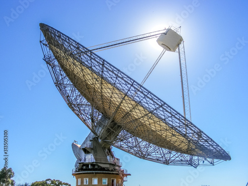 Photo A radio telescope with the sun behind it