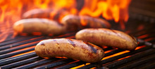 Brats Cooking Over Flaming Barbecue Grill