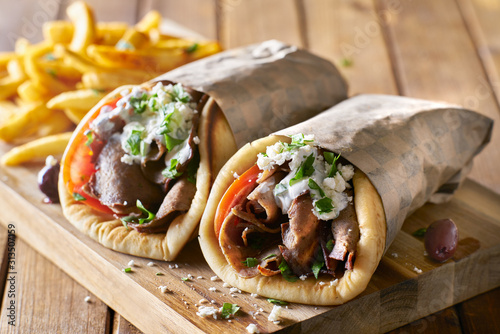 two greek gyros with shaved lamb and french fries - 313507159