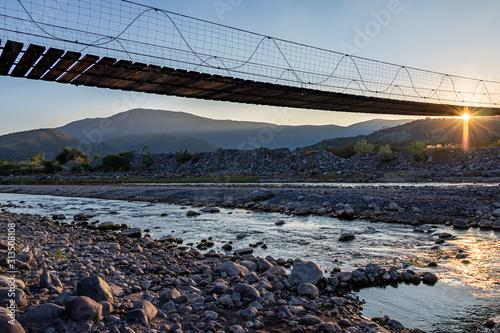 Puente colgante de madera sobre un rio lleno de rocas, cielo azul y plantas