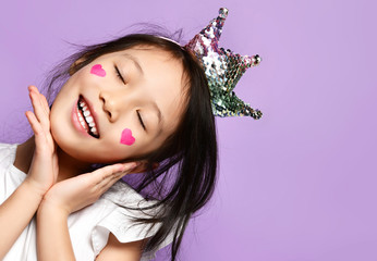 Asian Korean kid girl princess in crown closeup portrait Happy smiling laughing with a painted red hearts sign on cheeks
