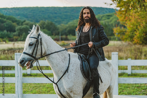 Fototapeta Handsome rider man on horse. Equestrian rides his white well looking horse. Handsome man riding horse at farm. Attractive male sitting on white stallion on the ranch in autumn. obraz