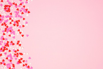 Valentines Day side border with candy heart sprinkles over a pink textured background. Copy space.