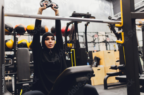 Valokuva Muslim asian woman in hijab exercizing in a gym.