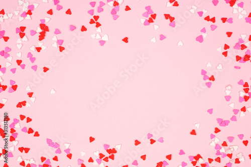 Fototapeta Valentines Day frame of candy heart sprinkles over a pink textured background. Copy space. obraz