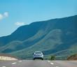 auto en carretera con paisaje de cerros y montañas