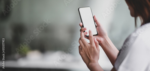 Close-up view of professional doctor using blank screen smartphone in her office room