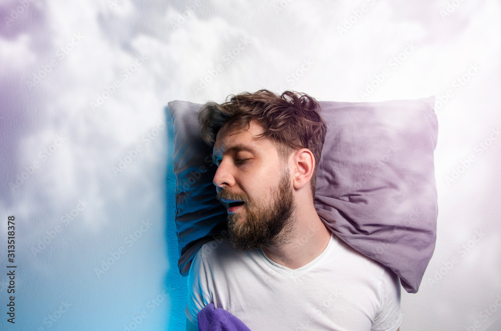 Fototapeta Man sound asleep , enjoying his nap, graphic clouds added , dreaming