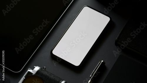 Cuadros en Lienzo Cropped shot of blank screen smartphone in dark modern office