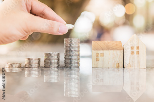 Fototapeta Hand choosing row of coin money on wood table and mini wood house, selective focus, Planning to buy property. Choose what's the best. A symbol for construction ,ecology, loan concepts obraz