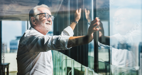Retirement concept. Senior grey-haired businessman standing and looking to right hand at modern business lounge high up in an office tower.