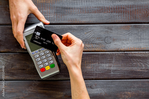 Fototapeta Contactless payment, paypass. Hand hold bank card near terminal on dark wooden background top-down copy space obraz